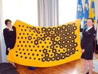 Aina Tarvis ja Jana Ots hoiavad kodutütarde sini-kollastes värvides vaipa