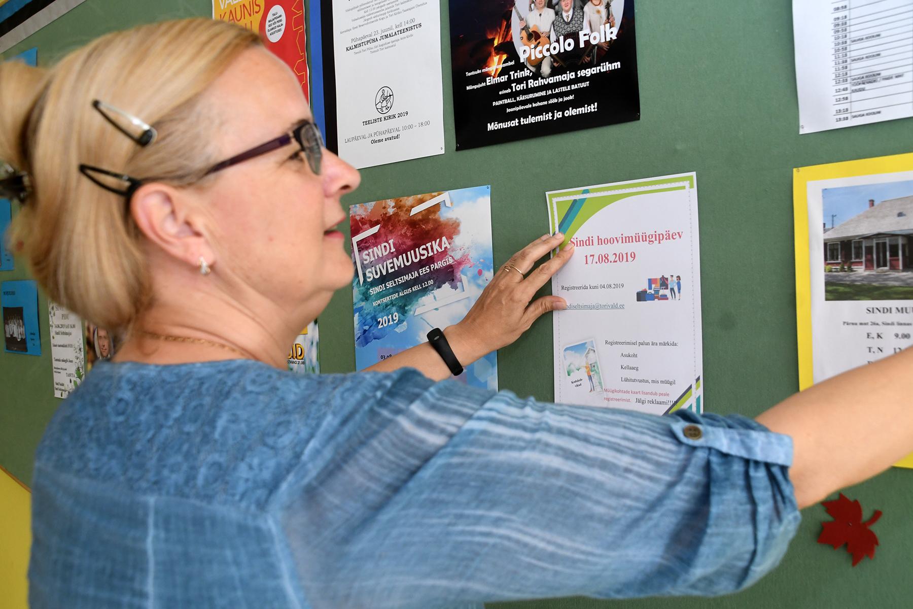 Anneli Uustalu kinnitab Sindi hoovimüügipäeva plakati teadetetahvlile. Foto Urmas Saard