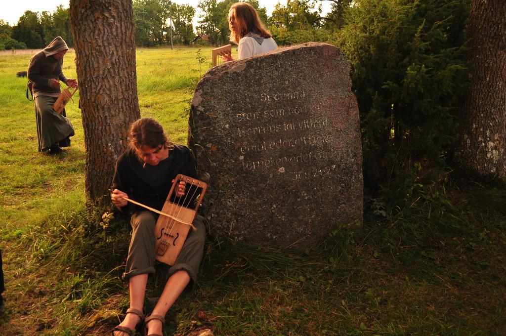 Eva Väljaots puu all hiiu kannelt harjutamas Vormsi hiiu kandle laagris 2012. aastal. Foto: Karoliina Kreintaal.