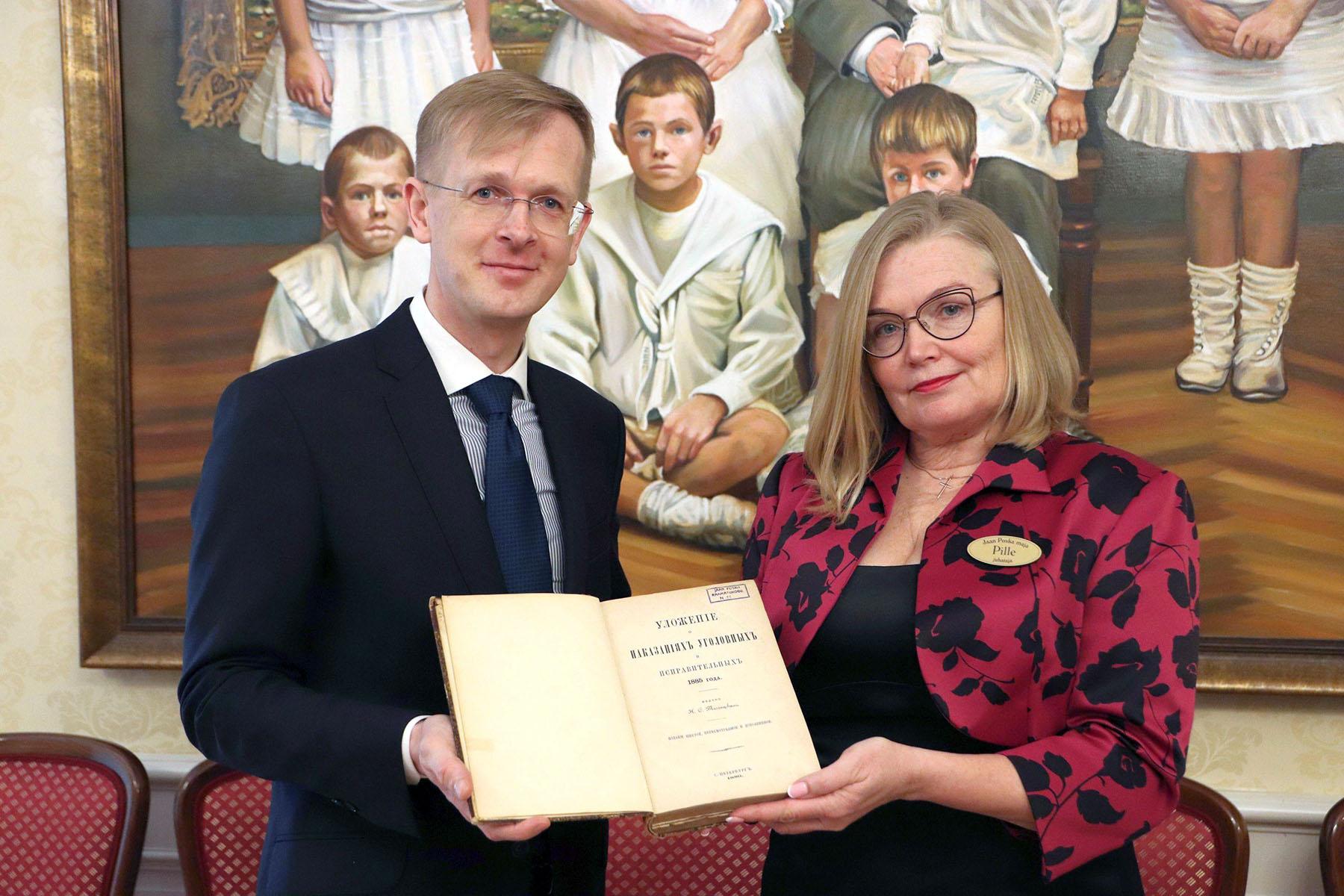 Linnavolikogu esimees Tiit Terik ja Poska maja juhataja Pille Lang kingitud raamatuga. Foto Jukko Nooni