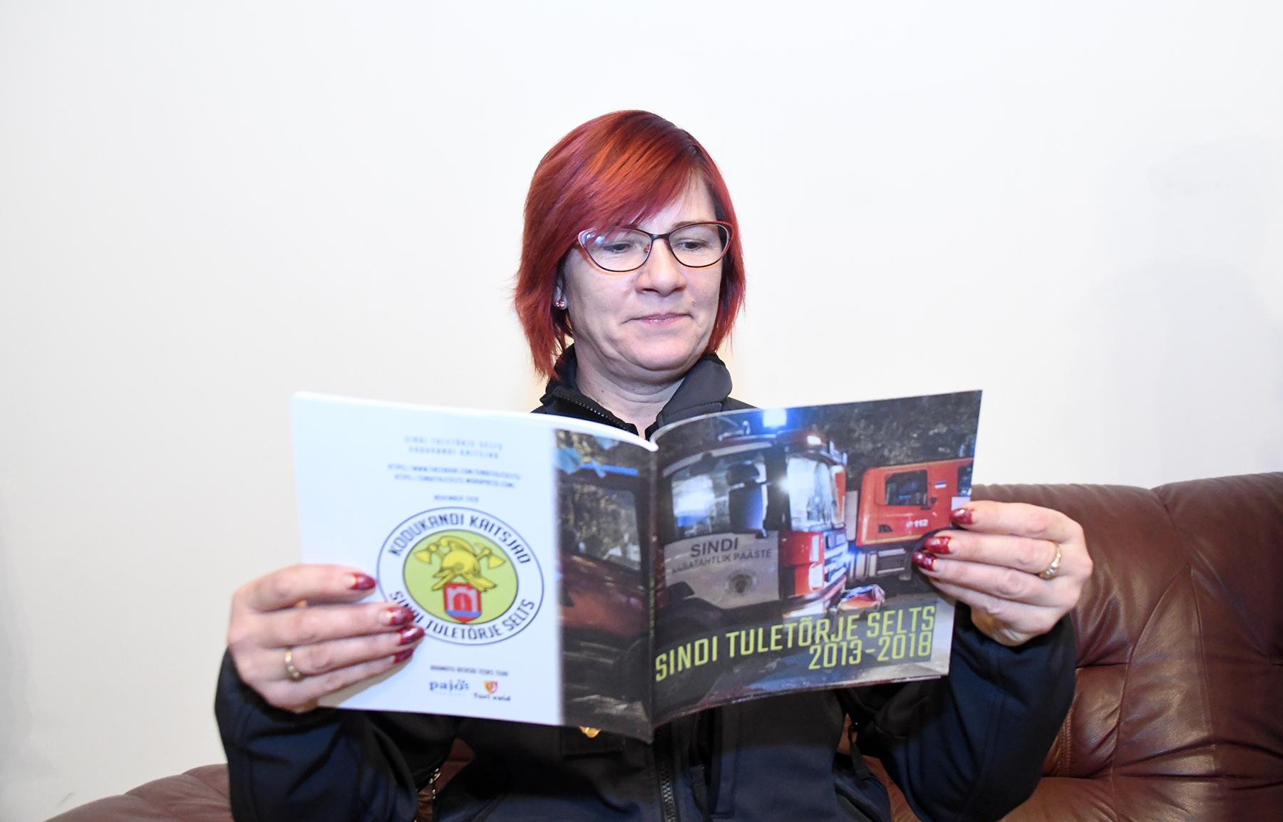Piirkonnapolitseinik Piret Dreimann lehitseb huviga äsja ilmunud kogumikku Sindi Tuletõrje Selts 2013-2018. Foto Urmas Saard