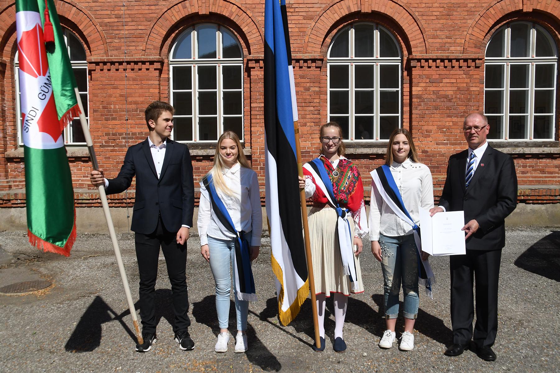 Sindi gümnaasiumi liputoimkond koos kooli lipu ja direktor Ain Keerupiga sinimustvalge lipu 135. sünnipäeval koolimaja õuel. Foto Urmas Saard