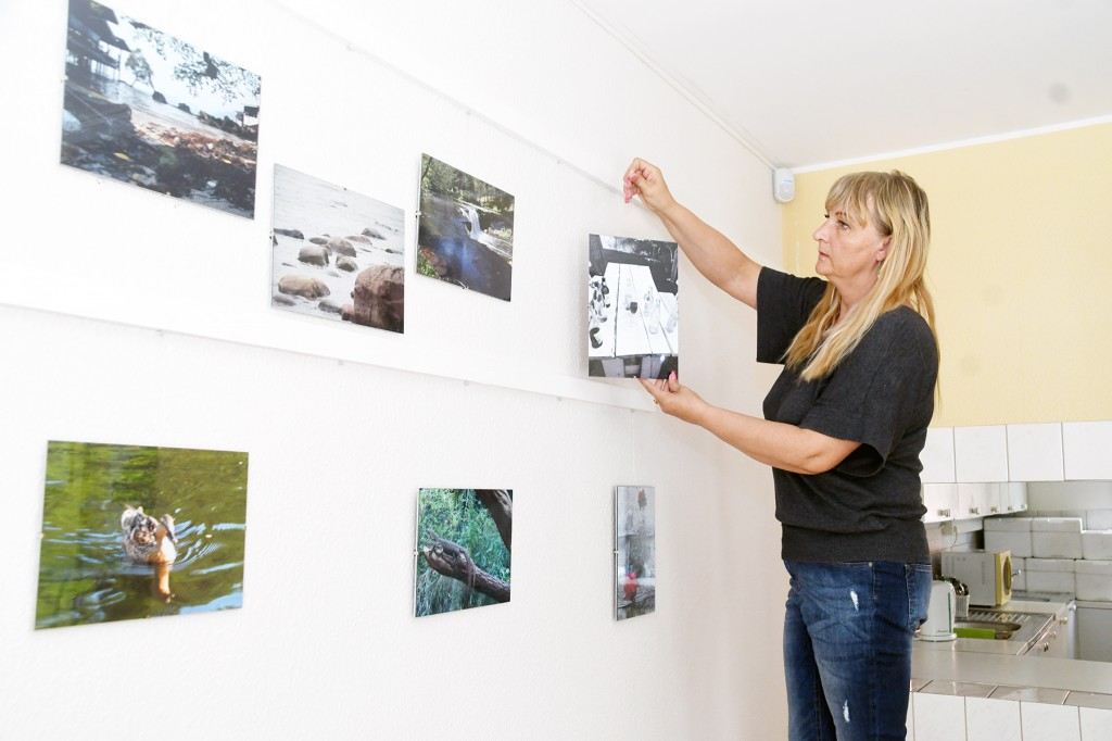 Sindi sotsiaaltöökeskuse juhataja Renna Järve paigutab Mikk Rätsepa fotosid seinale. Foto Urmas Saard